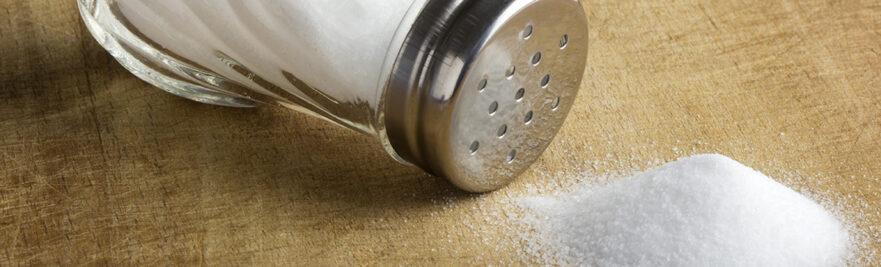 Spilled salt next to a salt shaker